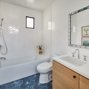 Modern inredning av ett litet vit vitt badrum för barn, med släta luckor, skåp i ljust trä, ett badkar i en alkov, en dusch/badkar-kombination, en toalettstol med hel cisternkåpa, vit kakel, keramikplattor, vita väggar, cementgolv, ett undermonterad handfat, bänkskiva i kvarts och blått golv