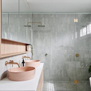 Пример оригинального дизайна: большая главная ванная комната в современном стиле с фасадами с утопленной филенкой, светлыми деревянными фасадами, отдельно стоящей ванной, двойным душем, серой плиткой, керамической плиткой, серыми стенами, полом из керамической плитки, настольной раковиной, столешницей из искусственного кварца, серым полом, душем с распашными дверями, белой столешницей, нишей, тумбой под одну раковину, подвесной тумбой и многоуровневым потолком