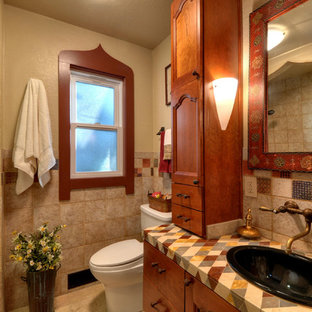 This is an example of a small mediterranean bathroom in San Francisco with a built-in sink, freestanding cabinets, medium wood cabinets, tiled worktops, an alcove bath, a shower/bath combination, a one-piece toilet, multi-coloured tiles, ceramic tiles, beige walls and travertine flooring.