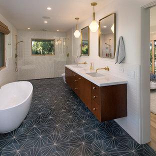 50 tals inredning av ett vit vitt en-suite badrum, med släta luckor, skåp i mörkt trä, ett fristående badkar, en kantlös dusch, vit kakel, vita väggar, ett undermonterad handfat, svart golv och med dusch som är öppen