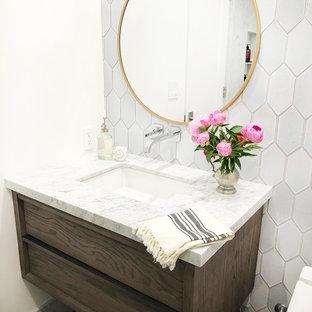 Modelo de cuarto de baño infantil, actual, pequeño, con puertas de armario de madera en tonos medios, bañera encastrada, combinación de ducha y bañera, sanitario de pared, baldosas y/o azulejos blancos, baldosas y/o azulejos de terracota, paredes blancas, suelo de baldosas de porcelana, lavabo bajoencimera, encimera de mármol, suelo gris, ducha con puerta con bisagras y encimeras blancas