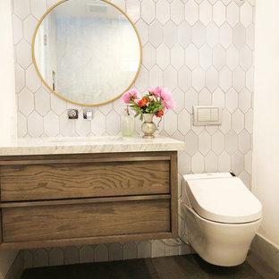 Ejemplo de cuarto de baño infantil, contemporáneo, pequeño, con puertas de armario de madera en tonos medios, bañera encastrada, combinación de ducha y bañera, sanitario de pared, baldosas y/o azulejos blancos, baldosas y/o azulejos de terracota, paredes blancas, suelo de baldosas de porcelana, lavabo bajoencimera, encimera de mármol, suelo gris, ducha con puerta con bisagras y encimeras blancas