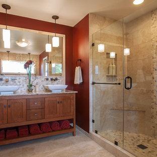 Immagine di una stanza da bagno padronale stile americano di medie dimensioni con lavabo a bacinella, ante con riquadro incassato, ante in legno scuro, top in marmo, vasca freestanding, doccia alcova, piastrelle beige, piastrelle in ceramica, pareti rosse e pavimento con piastrelle in ceramica
