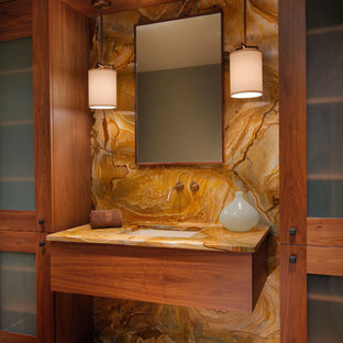 Foto de cuarto de baño actual con lavabo bajoencimera, armarios tipo vitrina, puertas de armario de madera oscura, baldosas y/o azulejos marrones, losas de piedra y suelo de madera en tonos medios