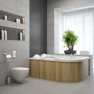 Esempio di una grande sauna minimalista con vasca idromassaggio, WC sospeso, piastrelle grigie, piastrelle di cemento, pareti grigie, pavimento con piastrelle in ceramica, pavimento grigio, ante lisce, ante in legno chiaro, lavabo sospeso e top in vetro