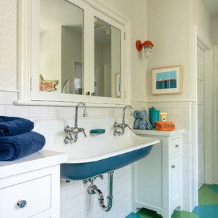 Réalisation d'une salle de bain champêtre pour enfant avec un placard à porte shaker, des portes de placard blanches, un carrelage blanc, des carreaux de céramique, un plan de toilette en quartz modifié, un plan de toilette blanc, un mur blanc, un sol en bois peint, un lavabo suspendu et un sol multicolore.
