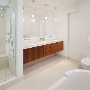 Trendy beige tile bathroom photo in Ottawa with an undermount sink, flat-panel cabinets, medium tone wood cabinets, a wall-mount toilet and white walls