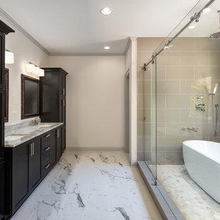 Foto de cuarto de baño principal, clásico renovado, de tamaño medio, con armarios estilo shaker, puertas de armario de madera en tonos medios, bañera exenta, ducha doble, sanitario de una pieza, baldosas y/o azulejos grises, baldosas y/o azulejos de porcelana, paredes blancas, suelo de mármol, lavabo bajoencimera y encimera de granito