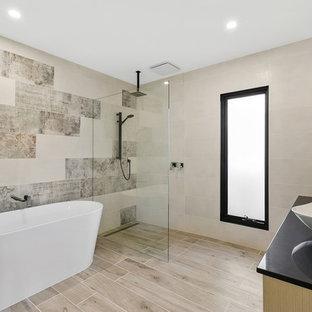 Ispirazione per una stanza da bagno design con ante beige, vasca freestanding, zona vasca/doccia separata, piastrelle beige, pareti beige, lavabo a bacinella, pavimento beige, doccia aperta e top nero