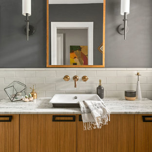Bathroom - mid-sized mediterranean white tile and subway tile multicolored floor bathroom idea in Tampa with flat-panel cabinets, medium tone wood cabinets, gray walls, a vessel sink, marble countertops and white countertops