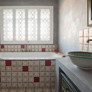 Mittelgroßes Mediterranes Kinderbad mit verzierten Schränken, dunklen Holzschränken, Einbaubadewanne, Toilette mit Aufsatzspülkasten, farbigen Fliesen, Terrakottafliesen, grauer Wandfarbe, Terrakottaboden, Aufsatzwaschbecken und Mineralwerkstoff-Waschtisch in Sussex
