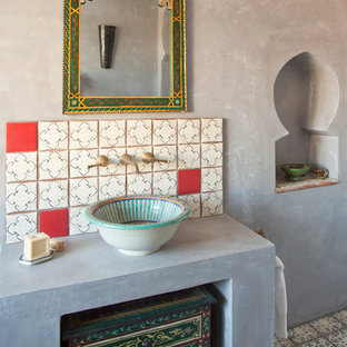 Design ideas for a medium sized mediterranean family bathroom in Sussex with freestanding cabinets, dark wood cabinets, a built-in bath, a one-piece toilet, multi-coloured tiles, terracotta tiles, grey walls, terracotta flooring, a vessel sink and solid surface worktops.