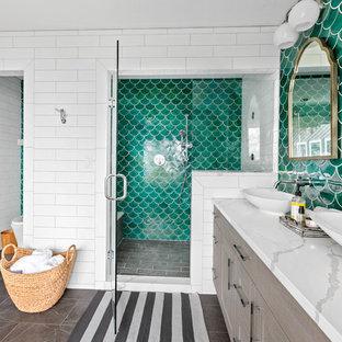 Diseño de cuarto de baño principal, marinero, grande, con puertas de armario grises, bañera exenta, ducha empotrada, sanitario de una pieza, baldosas y/o azulejos verdes, baldosas y/o azulejos en mosaico, paredes blancas, suelo de baldosas de porcelana, lavabo sobreencimera, encimera de cuarzo compacto, suelo gris, ducha con puerta con bisagras y encimeras blancas