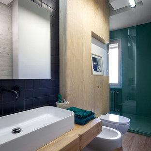 Ispirazione per una stanza da bagno industriale con doccia ad angolo, bidè, piastrelle nere, pareti verdi, lavabo a bacinella, top in legno, pavimento marrone, porta doccia scorrevole e top beige