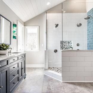 インディアナポリスの広いトランジショナルスタイルのおしゃれなマスターバスルーム (シェーカースタイル扉のキャビネット、青いキャビネット、コーナー設置型シャワー、白いタイル、磁器タイル、グレーの壁、クッションフロア、アンダーカウンター洗面器、クオーツストーンの洗面台、グレーの床、オープンシャワー、白い洗面カウンター、ニッチ、洗面台2つ、独立型洗面台、塗装板張りの天井、三角天井) の写真