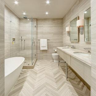Стильный дизайн: большая главная ванная комната в современном стиле с врезной раковиной, плоскими фасадами, светлыми деревянными фасадами, столешницей из известняка, отдельно стоящей ванной, угловым душем, унитазом-моноблоком, каменной плиткой, коричневыми стенами, полом из известняка и бежевой плиткой - последний тренд