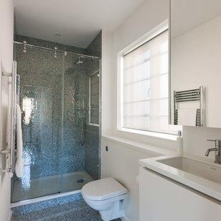Foto di una stanza da bagno minimalista con ante lisce, ante bianche, doccia aperta, WC sospeso, pareti bianche, pavimento con piastrelle a mosaico, lavabo sottopiano, top in superficie solida, pavimento blu, porta doccia scorrevole e top bianco