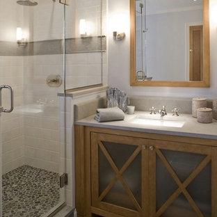 Exemple d'une salle de bain chic de taille moyenne avec un placard à porte vitrée, des portes de placard en bois brun, un carrelage gris, des carreaux de porcelaine, un mur bleu, un sol en galet, un lavabo encastré et un plan de toilette en onyx.