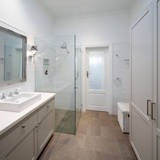 Photo of a mid-sized transitional bathroom in Sydney with shaker cabinets, blue cabinets, a drop-in tub, an open shower, a two-piece toilet, ceramic tile, light hardwood floors, a drop-in sink and engineered quartz benchtops.