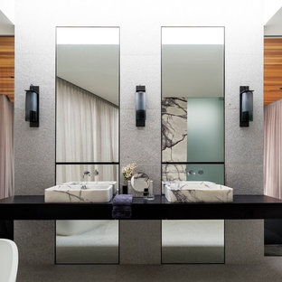 Contemporary master bathroom in Sydney with black cabinets, a freestanding tub, grey walls, a vessel sink and grey floor.