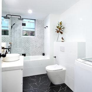 Свежая идея для дизайна: маленькая главная ванная комната в стиле модернизм с стеклянными фасадами, белыми фасадами, ванной в нише, открытым душем, унитазом-моноблоком, белой плиткой, керамической плиткой, белыми стенами, полом из цементной плитки, настольной раковиной, столешницей из искусственного камня, черным полом, открытым душем и белой столешницей - отличное фото интерьера