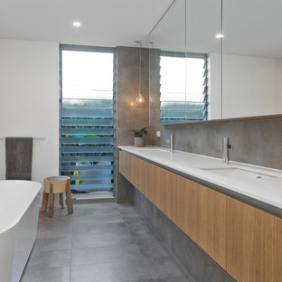 Modern master bathroom in Perth with flat-panel cabinets, medium wood cabinets, a freestanding tub, gray tile, white walls, an undermount sink, grey floor and white benchtops.