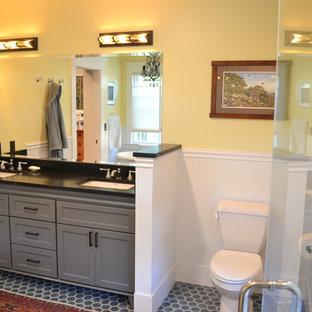 Foto di una stanza da bagno padronale stile americano di medie dimensioni con ante con riquadro incassato, ante grigie, WC a due pezzi, pareti gialle, pavimento con piastrelle in ceramica, lavabo sottopiano, pavimento grigio e top nero