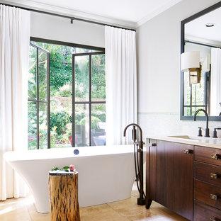 Esempio di una stanza da bagno padronale chic con consolle stile comò, ante in legno bruno, vasca freestanding, doccia alcova, piastrelle verdi, piastrelle di vetro, pavimento in pietra calcarea, lavabo da incasso e top in pietra calcarea