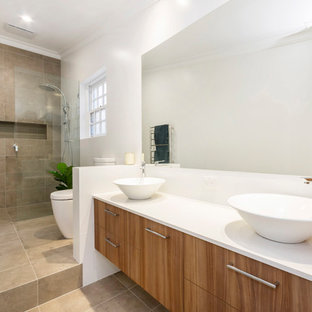 Design ideas for a contemporary 3/4 bathroom in Perth with flat-panel cabinets, medium wood cabinets, an alcove shower, a one-piece toilet, beige tile, white walls, a vessel sink, beige floor, an open shower and white benchtops.