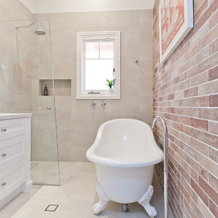 This is an example of a mid-sized transitional master bathroom in Perth with shaker cabinets, white cabinets, a claw-foot tub, a curbless shower, subway tile, beige walls, porcelain floors, an undermount sink, engineered quartz benchtops, beige floor, a hinged shower door, white benchtops and red tile.