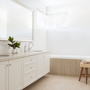 Design ideas for a large transitional 3/4 bathroom in Perth with recessed-panel cabinets, white cabinets, a drop-in tub, white tile, white walls, an undermount sink, beige floor, beige benchtops, a double vanity and a built-in vanity.