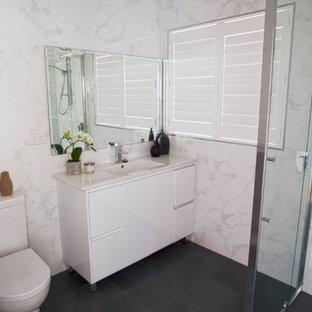 Ispirazione per una stanza da bagno design di medie dimensioni con ante con riquadro incassato, ante bianche, piastrelle multicolore, top in granito e top bianco