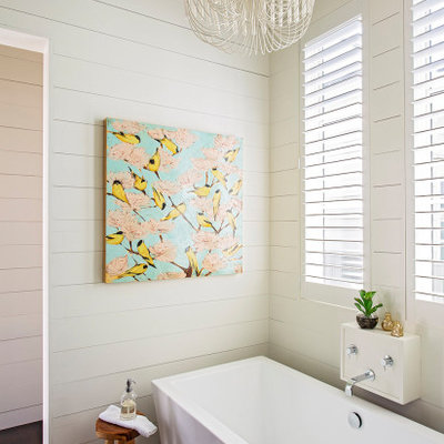 Example of a transitional dark wood floor, brown floor and shiplap wall freestanding bathtub design in Charleston with white walls