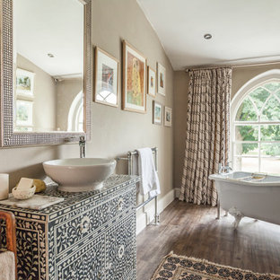 This is an example of a medium sized classic bathroom in Other with freestanding cabinets, a claw-foot bath, brown walls, dark hardwood flooring, a vessel sink and brown floors.