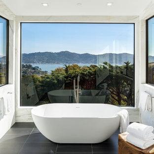 Foto de cuarto de baño principal, actual, grande, con bañera exenta, baldosas y/o azulejos blancos, losas de piedra, suelo de baldosas de porcelana y suelo negro