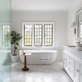 Foto på ett mycket stort vintage vit en-suite badrum, med marmorgolv, grått golv, luckor med infälld panel, vita skåp, ett fristående badkar, en hörndusch, vita väggar och ett undermonterad handfat
