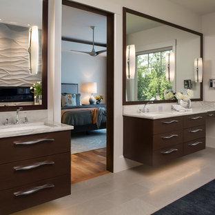 Foto på ett stort funkis en-suite badrum, med släta luckor, skåp i mörkt trä, ett fristående badkar, en hörndusch, en toalettstol med hel cisternkåpa, grå kakel, stenkakel, grå väggar, kalkstensgolv, ett undermonterad handfat och bänkskiva i kvartsit