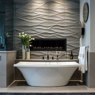 На фото: большая главная ванная комната в современном стиле с отдельно стоящей ванной, серой плиткой, каменной плиткой, серыми стенами и полом из известняка