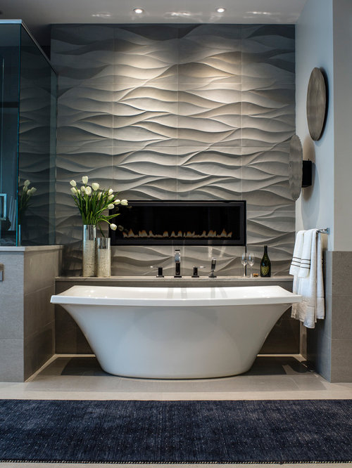 Large contemporary master gray tile and stone tile limestone floor  freestanding bathtub idea in Other with