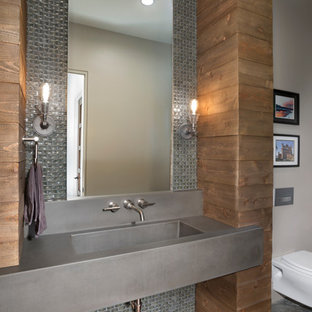 This is an example of a contemporary bathroom in Other with grey cabinets, a wall mounted toilet, grey tiles, metal tiles, beige walls, concrete flooring, an integrated sink, grey floors and grey worktops.