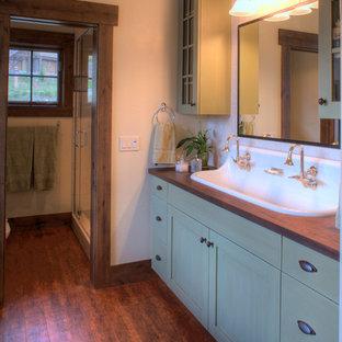 Ispirazione per una stanza da bagno padronale classica di medie dimensioni con ante in stile shaker, ante verdi, piastrelle beige, pareti beige, pavimento in legno massello medio, lavabo rettangolare, top in legno, pavimento marrone e top marrone
