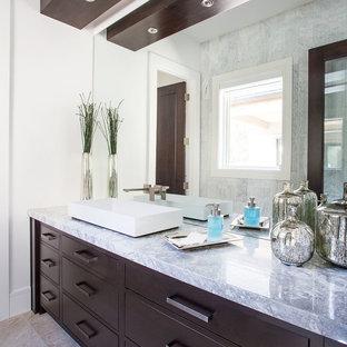 Создайте стильный интерьер: большая главная ванная комната в современном стиле с плоскими фасадами, темными деревянными фасадами, серой плиткой, белыми стенами, настольной раковиной, зеркальной плиткой, полом из керамогранита и мраморной столешницей - последний тренд