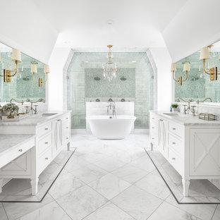 Klassisk inredning av ett vit vitt en-suite badrum, med luckor med infälld panel, vita skåp, ett fristående badkar, en dubbeldusch, vita väggar, ett undermonterad handfat, vitt golv och dusch med gångjärnsdörr