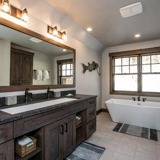 Diseño de cuarto de baño rural con armarios estilo shaker, puertas de armario de madera en tonos medios, bañera exenta, paredes blancas, suelo de baldosas de porcelana, lavabo de seno grande, encimera de granito, suelo beige y encimeras grises
