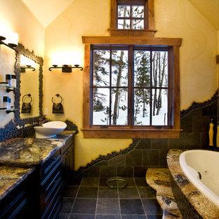 Ispirazione per una stanza da bagno padronale stile rurale di medie dimensioni con ante con riquadro incassato, ante nere, vasca da incasso, piastrelle nere, piastrelle in ardesia, pareti gialle, pavimento in ardesia, lavabo a bacinella, top in granito, pavimento nero e top multicolore