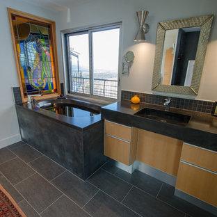 Diseño de cuarto de baño principal, bohemio, de tamaño medio, con lavabo integrado, armarios con paneles lisos, encimera de cemento, bañera esquinera, ducha empotrada, suelo de pizarra, puertas de armario de madera clara, paredes blancas y suelo gris