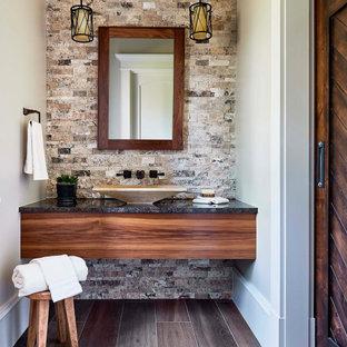 Ejemplo de cuarto de baño rústico con puertas de armario de madera oscura, baldosas y/o azulejos multicolor, paredes beige, lavabo sobreencimera, suelo marrón y encimeras negras