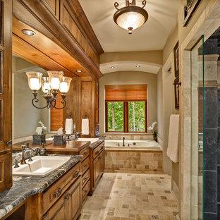Inspiration för ett stort vintage en-suite badrum, med luckor med upphöjd panel, skåp i mellenmörkt trä, ett platsbyggt badkar, en dusch i en alkov, en toalettstol med separat cisternkåpa, beige kakel, stenkakel, beige väggar, travertin golv, ett nedsänkt handfat och granitbänkskiva