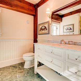 Modelo de cuarto de baño rural con armarios tipo mueble, puertas de armario blancas, sanitario de dos piezas, paredes blancas, suelo de mármol, lavabo bajoencimera, encimera de mármol y suelo verde