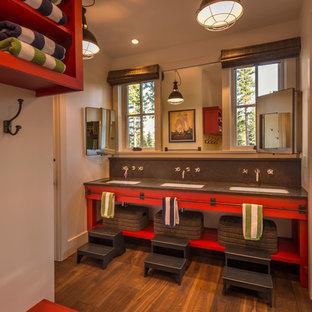Cette photo montre une grand salle de bain montagne avec un placard sans porte, des portes de placard rouges, un mur blanc, un sol en bois brun, un lavabo encastré et un plan de toilette en béton.